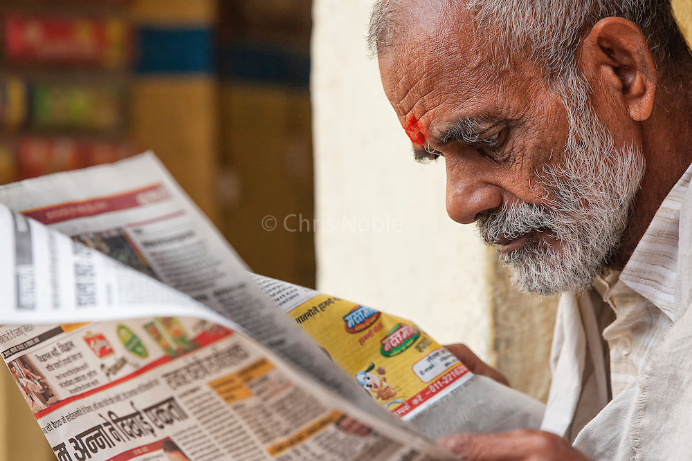 "A man reading a newspaper in the ""galis"" (alley ways) of the Old City of Varanasi India."