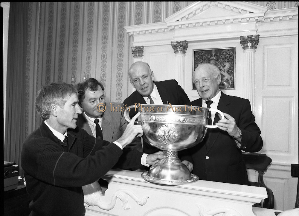 Replica Of Sam Maguire Cup Assayed.  (R85)..1988..18.08.1988..08.18.1988..18th August 1988..The Sam Maguire Cup which was first won by 1928 All Ireland Champions, Kildare is being replaced by a replica for the 1988 final. The original cup was wrought by Hopkins and Hopkins of Dublin to the design of the Ardagh Chalice and is made of silver..The replica has been made by Kilkenny based silversmith Mr Desmond Byrne. the silver for the replica wa presented to the GAA by Mr Kieran Eustace, Managing Director, Johnson Matthey, Grafton Street, Dublin. The replica is hand crafted to match the eacct design and dimensions of the original. Today in Dublin Castle the new 'Sam Maguire' was stamped with the Millennium Stamp by the Assay Master, Dublin Castle...Image shows the new 'Sam Maguire' being examined by Mr Desmond Byrne, Silversmith,Kilkenny who made the replica, Mr Lorcan O'Rourke,Development manager, GAA, Mr Kieran Eustace,Managing Director, Johnson Matthey Ltd and Mr Ronnie LeBas,retired, Assay Master of the Goldsmiths Co,Dublin Castle after the stamping of the cup with the Millennium stamp.