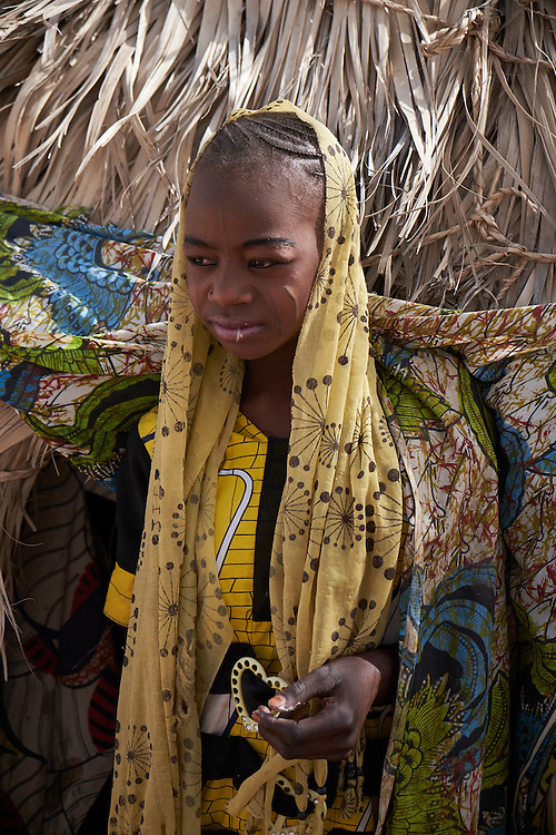 Fatima Brah, 16 years old stands outside a shelter in the village of Guidan Kaji near the border with Nigeria on the outskirts of Diffa, Niger on February 13, 2016. Displaced people from Niger and Nigeria are sheltering in the village after fleeing at the nearby border. Many of the families had witnessed attacks by Boko Haram in their villages or had fled because of other villages around them being attacked. Caritas undertook a distribution of sleeping covers, mosquito nets, pots and money transfers. <br /> <br /> '9 months ago we came here after Boko Haram burnt down our village during the night and we fled into the bush. They killed more than ten people. We left with nothing, not even clothes or food. We threw the children in the car and the rest of us came here on foot. All the clothes we are wearing were given to us by the people in a nearby village.'