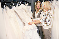 Mother and daughter looking at each other while selecting wedding gown in bridal store