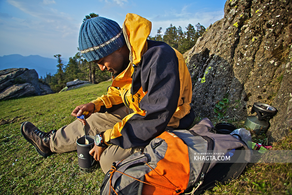 Tipu, a Mountaineer, making lemon tea as the sun sets the horizon at Churdhar Peak, Shimla, Himachal Pradesh, India
