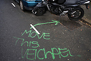 A request to move this vehicle has been mis-spelled in sprayed aerosol on the road's surface in a residential London street