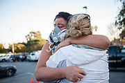 MALIBU, CA - Keely Shaye Brosnan, wearing a respirator to protect against dust an ash in the air, embraces a friend at an ad hoc aid station created at an elementary school in the Point Dume neighborhood in the aftermath of the Woolsey Fire in Malibu, California, Monday Nov. 12, 2018. Brosnan's home had been narrowly saved from the Woolsey Fire days earlier.