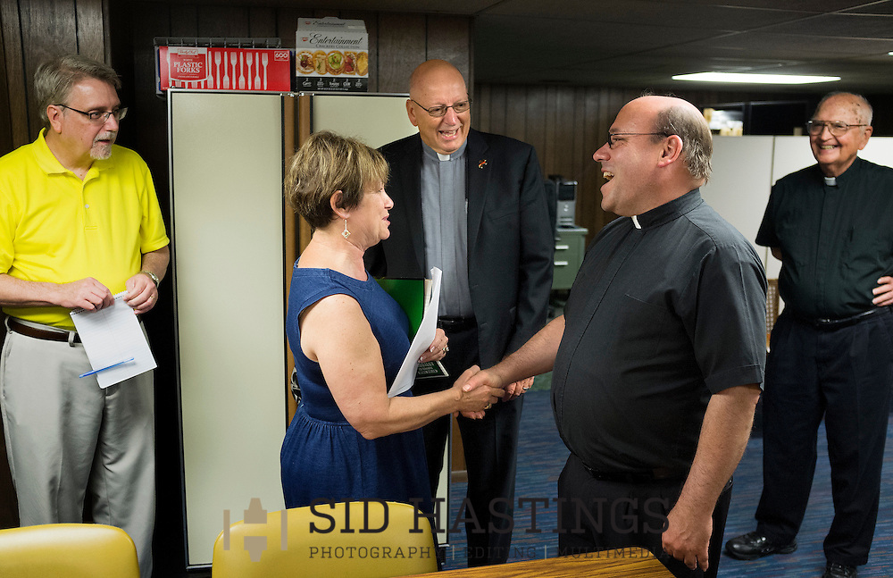 28 JULY 2015 -- ST. CHARLES, Mo. -- The Rev. Mark Whitman (second from right) and Deacon John Schiffer (third from right) greet Pastoral Associate Jan McArthur (second from left) and Music Director Tim Aubuchon (left) before a meeting of clergy and staff at St. Robert Bellarmine Catholic Church in St. Charles, Mo., Tuesday, July 27, 2015. Also pictured is Monsignor Ray Hampe (right), in residence at St. Robert Bellarmine. Deacon Schiffer and Father Whitman will lead the parish following the departure of previous pastor Father Patrick Ryan. Photo © copyright 2015 Sid Hastings.