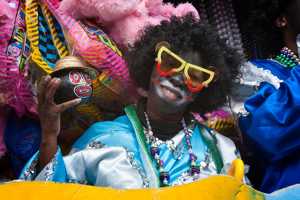 A member of the Zulu Social Aid and Pleasure Club poses with a hand-decorated coconut on one of the floats in the Krewe of Zulu Parade on Mardi Gras day near Claiborne Avenue in New Orleans, Louisiana, USA.