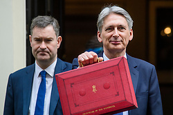 © Licensed to London News Pictures. 08/03/2017. London, UK. DAVID GAUKE MP stands next to British chancellor PHILIP HAMMOND holding up his ministerial red box as he leaves 11 Downing Street in London before delivering his 2017 Budget to Parliament. Photo credit: Ben Cawthra/LNP