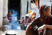 Sadma Khan (extreme left, in purple), 19, makes lunch in the shared compound of her mother's (in orange) extended family's house in a slum area of Tonk, Rajasthan, India, on 19th June 2012. She was married at 17 years old to Waseem Khan, also underaged at the time of their wedding. The couple have an 18 month old baby (in red) and Sadma is now 3 months pregnant with her 2nd child and plans to use contraceptives after this pregnancy. She lives with her mother since Waseem works in another district and she can't take care of her children on her own. Photo by Suzanne Lee for Save The Children UK