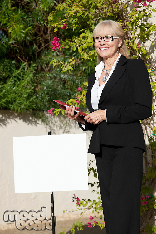 Happy senior woman standing by sign board with clipboard