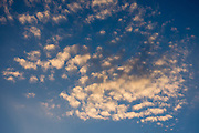 Sunset highlights dappled white cloud pattern in blue sky above Slovenia, Europe.