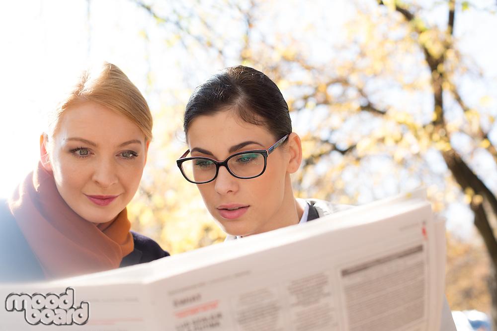 Businesswomen reading newspaper at park