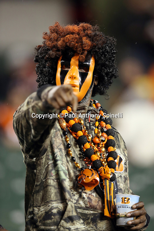 A Cincinnati Bengals fan points while wearing a team colored face mask, wig, and beads while wearing military clothes on honor of the NFL's Salute to Service military appreciation initiative during the 2015 week 10 regular season NFL football game against the Houston Texans on Monday, Nov. 16, 2015 in Cincinnati. The Texans won the game 10-6. (©Paul Anthony Spinelli)