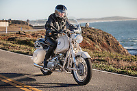 Brent Greenwood (MR) riding his 1960s BMW R60US motorcycle (PR) on a coastal road in Sonoma County.