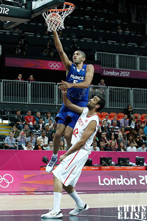 04 August 2012: France Nicolas Batum goes for the layup past Tunisia Makram Ben Romdhane during 73-69 Team France victory over Team Tunisia, during the men's basketball preliminary, at the Basketball Arena, in London, Great Britain.