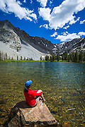 Hiker enjoying the view at Fern Lake, Ansel Adams Wilderness, June Lake, California USA