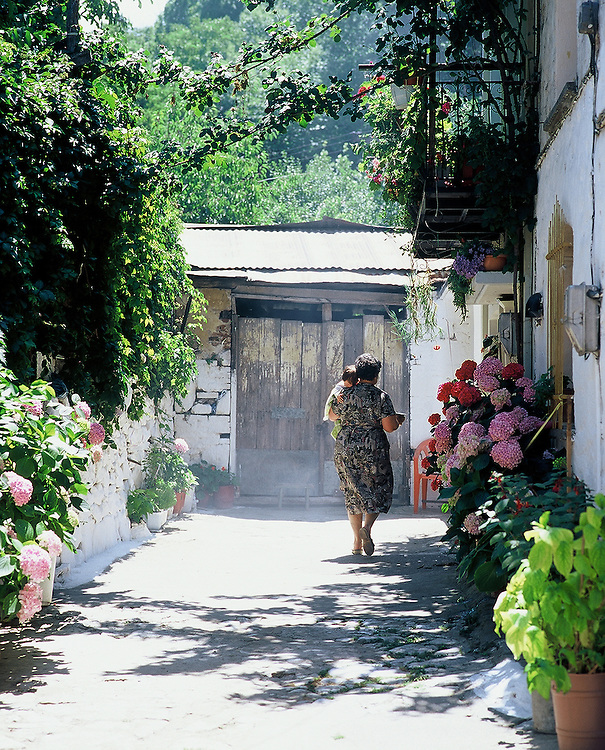 Woman carrying baby walks down quite street in Agiassos on the Island of Lesvos in Greece.