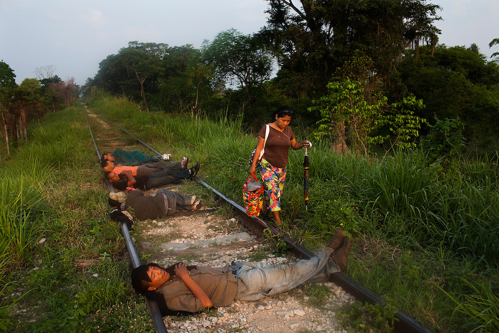 Migrants sleep on the railroad tracks in Tenosique, Tabasco.  Tenosique is the starting point for migrants who will travel on top of a freight train north to the border with the United States.  They sleep on the tracks to be sure that they can hear, and feel, approaching trains and won't miss them. The trip for these migrants, mostly from Central America,  has become increasingly dangerous over the past several years as Mexico's drug war has raged and kidnappings and killings of migrants has increased.