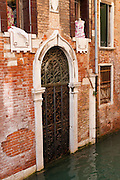 "A canal of the Venice Lagoon laps across the sill of a historic doorway shuttered with iron. Built on a sinking marsh, Venice floods often due to tides and weather. On one island, a Roman walkway is now 5 feet below sea level. Industrial pumping of groundwater (now banned) sank Venice by 10 centimeters from 1920-1970. Global warming now raises sea levels by 3.2 centimeters (1.3 inches) per decade, much faster than the marsh sediments are compacting downwards. An overwhelming consensus of world scientists agree that global warming is indeed happening and humans are contributing to it through emission of heat-trapping ""greenhouse gases,"" primarily carbon dioxide (see www.ucsusa.org). Since the industrial revolution began, humans have increased atmospheric CO2 concentration by 35% (through burning of fossil fuels, deforesting land, and grazing livestock). The Republic of Venice wielded major sea power during the Middle Ages, Crusades, and Renaissance. Riches from Venice's silk, grain, and spice trade in the 1200s-1600s built elaborate architecture combining Gothic, Byzantine, and Arab styles. Venice and the Venetian Lagoon are honored on UNESCO's World Heritage List."