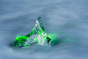 Ice floating in the arctic ocean at Iceland's famed Joklusarlon glacial lagoon. Iceberg was lite with green laser light.