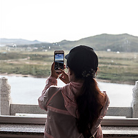 HUNCHUN, 09/12/2017:<br />  Chinese tourists look at North Korea from a viewpoint in Fangchuan.