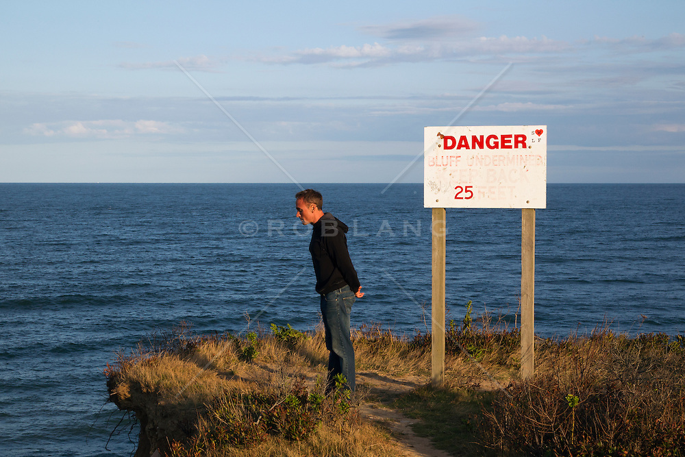 man standing on a cliff by a warning sign in Montauk, NY