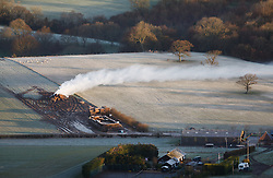 © Licensed to London News Pictures. 05/03/2014. Butser Hill, Hampshire, UK. Smoke from a pile of burning hay moves across the landscape at low level. Sunrise across the South Downs National Park, today 5th February 2014. Photo credit : Rob Arnold/LNP