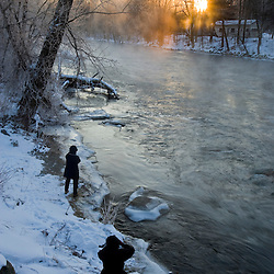 Photographers photograph a winter sunrise over the Ashuelot River in Winchester, New Hampshire.