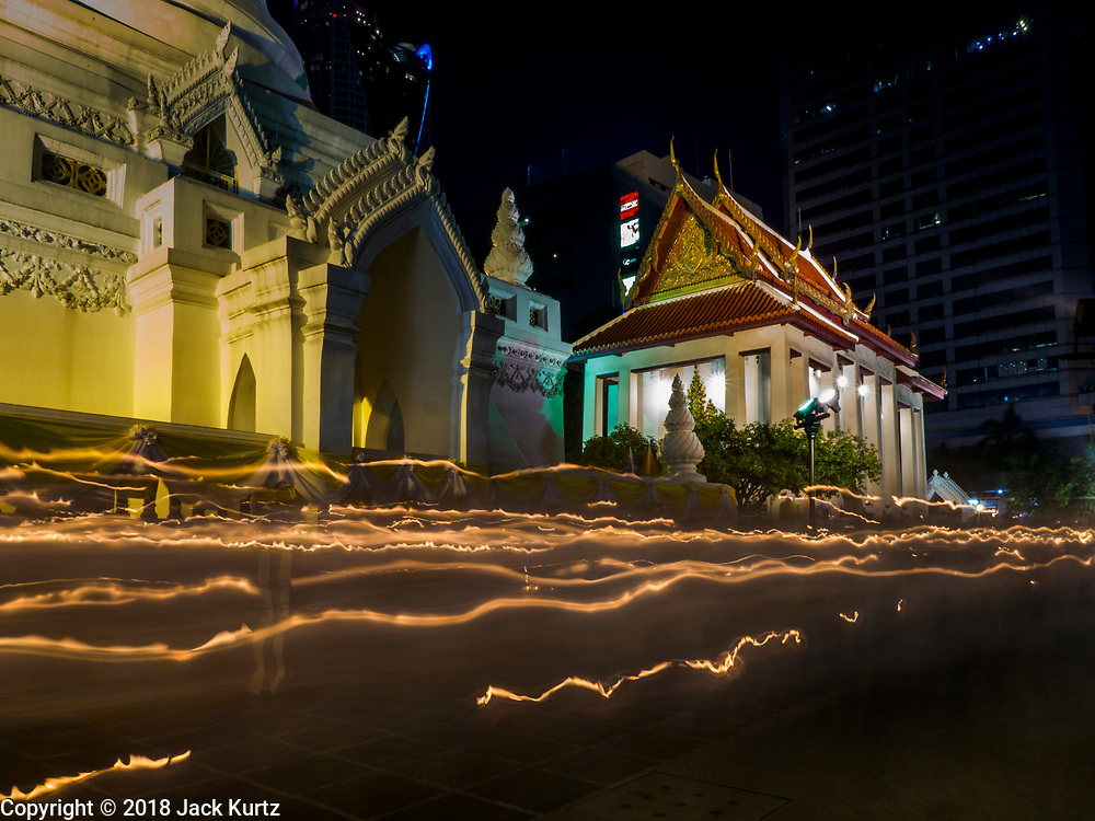 "01 MARCH 2018 - BANGKOK, THAILAND:    A time exposure of people walking in a candlelight procession around Wat Pathum Wanaram in central Bangkok. Many people go to temples to perform merit-making activities on Makha Bucha Day, which marks four important events in Buddhism: 1,250 disciples came to see the Buddha without being summoned, all of them were Arhantas, or Enlightened Ones, and all were ordained by the Buddha himself. The Buddha gave those Arhantas the principles of Buddhism. In Thailand, this teaching has been dubbed the ""Heart of Buddhism.""    PHOTO BY JACK KURTZ"