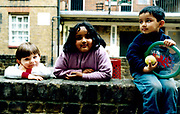 Three children sitting and leaning on a brick wall.