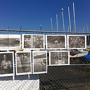 &quot;Mira Mexico&quot;, newspaper exhibition installed on a fence by a boatyard by a former U.S. Navy Base in Seattle, Washington July 5, 2013.<br /> (Credit Image: &copy; Kelly Mallahan)<br /> <br /> Curator<br /> Kelly Mallahan (USA)<br /> <br /> Using photographs taken by Louie Palu relating to the Mexican drug war, this project challenges the reader to take apart this newspaper to see the full photographs and view the content. The goal is to force the reader to dismantle the vehicle used to deliver news and facts and thereby empower the reader to begin to think more critically. There are 16 photos in total, eight that do not relate to violence and eight that focus on violence or the drug business.. Each photograph is printed on a single sheet of newsprint, so if you take the newspaper apart each sheet of paper will have only one photograph on each side. Only eight pictures can be viewed at one time No photo can be entirely seen unless the reader opens and takes the newspaper apart. <br /> <br /> Once the newspaper comes apart it can be put back together in any order the reader wishes. The page spreads can also be hung as an exhibition. With violent images on one side and non-violent images on the other, the reader must become editor, curator or even censor, choosing how many violent photos are seen vs. how many non-violent photographs are seen. This forces the reader to face up to the fact that all delivery of news involves choices, of what to show and tell and what not to show and tell. It also forces the reader to face up to the system of institutions that serves as the gatekeepers in journalism and the visual arts. The questions are obvious. Is the editor censoring? Is the edit a true depiction of the news and the issue? Are violent images being used effectively to tell a story, or to sensationalize the story? The actual newspaper as an object forces the reader to engage in a a multidimensional exercise in journalism, art, and the politics of representation and message manipulation.
