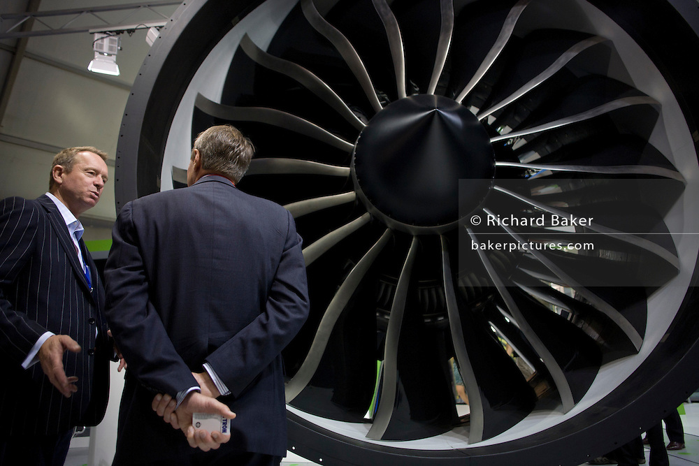 An employee and potential buyer discuss potential business deals at the General Electric (GE) jexhibition stand during the Farnborough Airshow. The et engine manufacturer's main exhibit is a real GEnx turbofan engine that GE claim emits 15% less Co2 than conventional engines. The GEnx (General Electric Next-generation) is an advanced dual rotor, axial flow, high bypass turbofan in production by GE Aviation for the Boeing 787 and 747-8. The GEnx is intended to replace the CF6 in GE's product line.