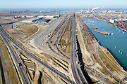 Nederland, Zuid-Holland, Rotterdam, 18-02-2015; Euopaweg buigt af naar de Maasvlakte en Tweede Maasvlakte (MV2).   Emplacement Maasvlakte, Distripark en water van de Hartelhaven. Infrabundel van autosnelweg N15, spoorweg (Betuweroute) en hoogspanningsleidingen. <br /> New and man-made land in the North sea designated for the Port of Rotterdam. Infrastructure bundle: motorway, railway (Betuweroute) and power lines.<br /> luchtfoto (toeslag op standard tarieven);<br /> aerial photo (additional fee required);<br /> copyright foto/photo Siebe Swart