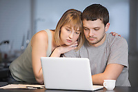 Young couple sit at laptop in kitchen