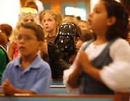 (10/08/2008 New Port Richey) First grader Marc Flores, dressed as Darth Vader, stands out from the crowd as he brings his gloved hands together in prayer beside classmates during the weekly chapel service Wednesday morning in the sanctuary at Elfers Christian School. Flores and other students in kindergarten through fifth grade dressed up as their favorite story book character as part of the Book It! reading incentive program. SUMMARY: Elfers Christian School has a book it parade, kids dressed up as their favorite story book character
