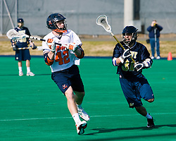Virginia midfielder Max Pomper (42) passes past Navy midfielder Matt Bitter (31).  The Virginia Cavaliers scrimmaged the Navy Midshipmen in lacrosse at the University Hall Turf Field  in Charlottesville, VA on February 2, 2008.
