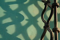 Central America, Guatemala, Antigua, shadows on wall and wrought-iron rail