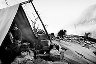 A grandmother with her grandchildren on the outskirts of Balakot. A tarpaulin stretched over a post is their cold and windy home on the roof of the town's collapsed hotel. <br /> Balakot - Nov. 2005
