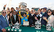 Victor Espinoza shows off both the Belmont Trophy and his new 18K gold Longines Conquest Classic timepiece after a historic victory at the 147th Belmont Stakes at Belmont Park Race Track, securing the first Triple Crown win in 37 years, Saturday, June 6, 2015 in Elmont, N.Y. Longines is the official timekeeper of the Triple Crown. (Photo by Stuart Ramson/Invision for Longines/AP Images)