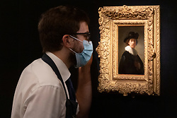© Licensed to London News Pictures. 23/07/2020. London, UK. A Sotheby's staff member views a painting titled self portrait, wearing a ruff and black hat painting (1632) by artist Rembrandt Van Rijn with an estimate of £12-16 million. Works spanning over half a millennium of art history go on display at Sotheby's London ahead of a one-off auction on July 28. Titled 'Rembrandt to Richter', the sale will offer the very best from Old Masters, Impressionist & Modern Art, Modern & Post-War British Art and Contemporary Art – travelling from the Italian Renaissance through to Pop Art. Photo embargoed for usage until 24th July 2020 09:00. Photo credit: Ray Tang/LNP