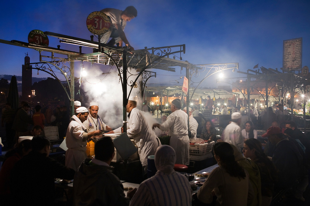 Vendors sell food among the lights and crowds of Djemaa el Fna at night