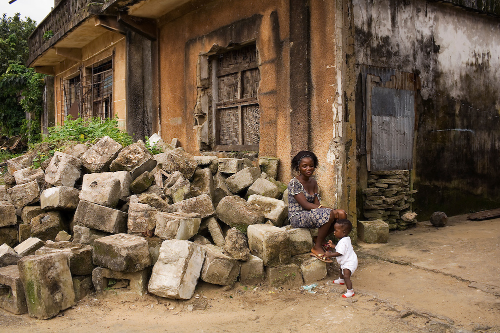 Mantou Syllah, 18 with her one year old baby God Gave, they live in a derelect bit one of the many buildings destroyed during the war. Fanti town, fishermens community, Buchanan, Liberia.