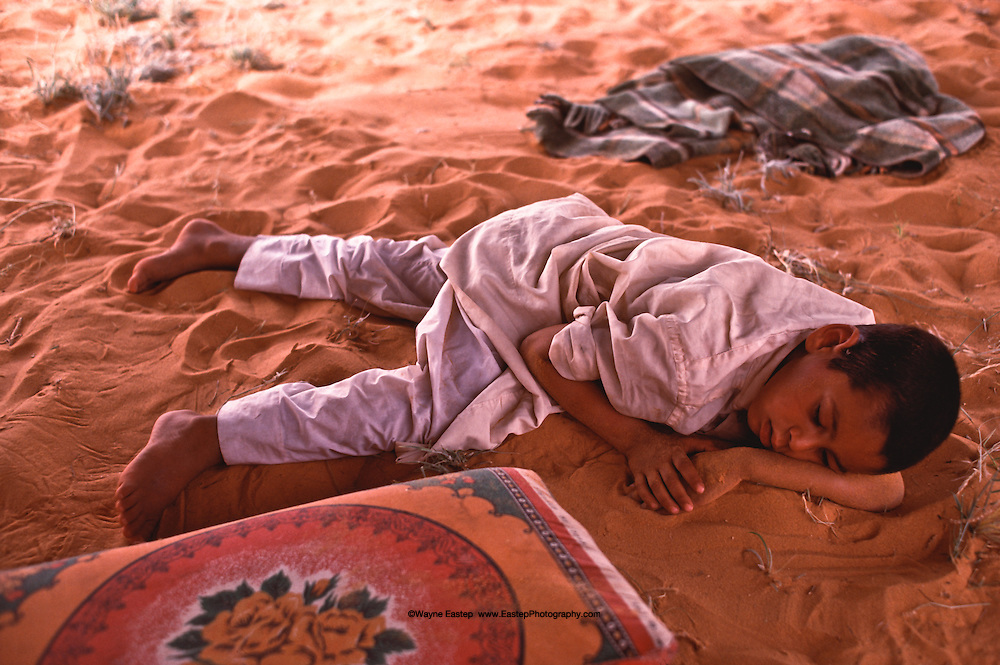 Al Amrah boy napping during the hottest part of the day.  In the summer temperatures can reach 125 degrees F. Dahna Sands, Saudi Arabia