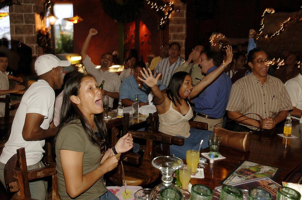 German: Sports-Bar Trotters in Port of Spain, Trinidad. Fans verfolgen die Auslosung der Gruppen der Fussball-WM in Deutschland 2006.