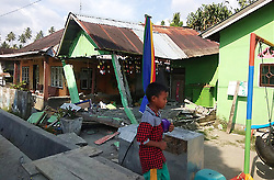 Sept. 28, 2018 - Sulawesi, Indonesia - A boy walking in front of a collapsed house in Donggala, Indonesia's Central Sulawesi province. At least 48 people were killed and 356 others injured as strong earthquakes and ensuing tsunami rattled Indonensia's Central Sulawesi province on Friday, a disaster agency official said on Saturday. (Credit Image: © Indonesian National Board for Disaster Management/Xinhua via ZUMA Wire)