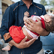 Bashir 29 holding his 7 months old girl Hamid from Chardere district of Afghanistan in Moria camp, Lesvos, Greece