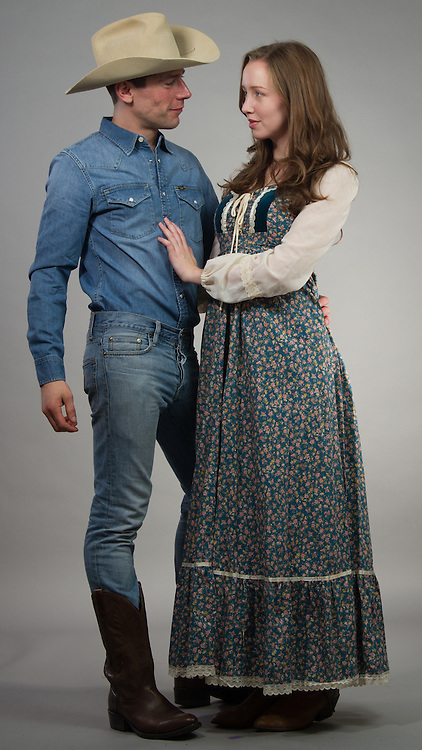 Couple posing together in western outfits.