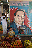 Fruit vendor under a political poster, Koyambedu Fruit Market, Chennai, Tamil Nadu, India