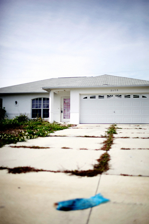 Grass seeps through the cracks in a driveway of a vacant home on SW 29th Avenue in Cape Coral, Fla. on Feb. 8, 2010. Cape Coral and Lehigh Acres, Fla. have been crippled in the nation's foreclosure crisis, putting Lee County in the national spotlight.