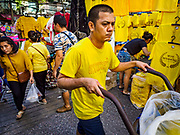 03 JULY 2018 - BANGKOK, THAILAND: A porter pushes his handtruck past shops selling yellow shirts in Bobae Market. The birthday of King Maha Vajiralongkorn Bodindradebayavarangkun, Rama X, is 28 July. The King, the only son of Thailand's late King Bhumibol Adulyadej, became the King of Thailand in 2016 after the death of his father. King Vajiralongkorn was born on 28 July 1952, a Monday. In Thai culture each day of the week has a color, and yellow is the color is associated with Monday, so people wear yellow for the month before his birthday to honor His Majesty.   PHOTO BY JACK KURTZ