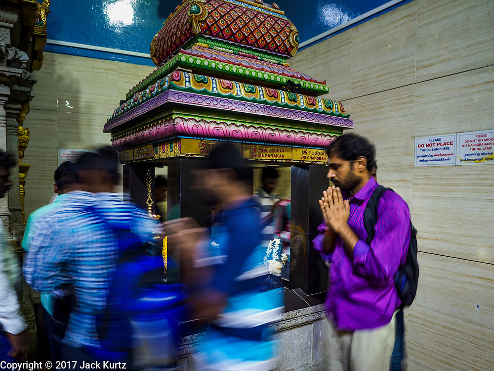 "09 JULY 2017 - SINGAPORE: Hindu guest workers in Singapore walk around a deity in Sri Veeramakaliamman Temple in Singapore's ""Little India."" There are hundreds of thousands of guest workers from the Indian sub-continent in Singapore. Most work 5 ½ to six days per week. On Sundays, the normal day off, they come into Singapore's ""Little India"" neighborhood to eat, drink, send money home, go to doctors and dentists and socialize. Most of the workers live in dormitory style housing far from central Singapore and Sunday is the only day they have away from their job sites. Most work in blue collar fields, like construction or as laborers.    PHOTO BY JACK KURTZ"