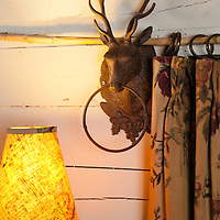 Rustic Cabin: Detail of iron stag head curtain rod bracket